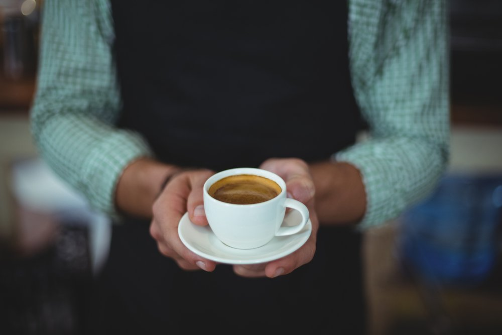 Mid section of waiter holding cup of coffee in cafe